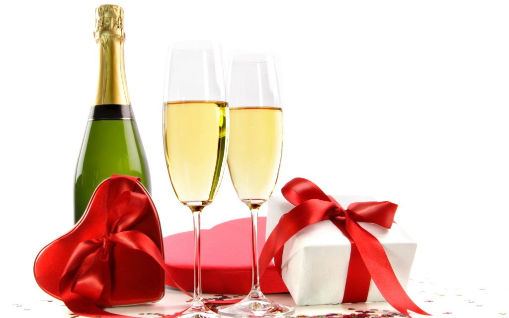 Glasses of champagne with bottle and gifts on white